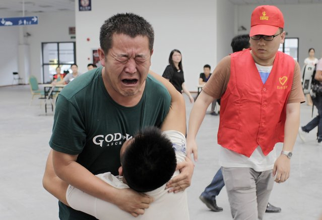 Family members cry at a caring centre for relatives of victims of a factory explosion, in Kunshan, Jiangsu province August 3, 2014. China suffered its worst industrial accident in a year on Saturday when an explosion killed at least 69 people and injured more than 120 at a factory that makes wheels for U.S. carmakers, including General Motors. (Photo by Reuters/Stringer)