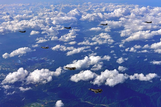 This handout photo taken on August 31, 2017 and provided by South Korean Defence Ministry in Seoul shows South Korean F-15K fighter jets and US F-35B stealth jet fighters flying over South Korea during a joint military drill aimed to counter North Korea's latest missile test. US heavy bombers and stealth jet fighters took part in a joint live fire drill in South Korea on August 31, intended as a show of force against the North after its latest missile launch, Seoul said. (Photo by AFP Photo/South Korean Defence Ministry)