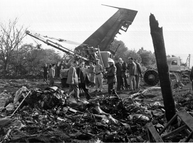 Firemen and civilians survey the scene of devastation around the wreckage of a chartered Air France aeroplane which crashed whilst taking off from Orly Airport, June 3, 1962. (Photo by AP Photo)