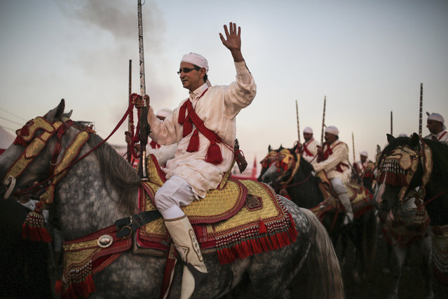 In this Thursday, August 17, 2017 photo, a horseman waves to the crowd after a successful charge during Tabourida, a traditional horse riding show also known as Fantasia, in Mansouria, near Casablanca, Morocco. (Photo by Mosa'ab Elshamy/AP Photo)