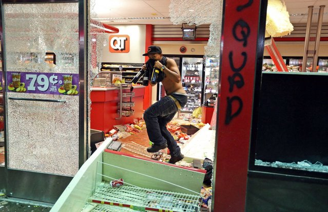 A man leaves a store on Sunday, August 10, 2014, in Ferguson, Mo. A few thousand people crammed a suburban St. Louis street Sunday night at a vigil for unarmed 18-year-old Michael Brown shot and killed by a police officer, while afterward several car windows were smashed and stores were looted as people carried away armloads of goods as witnessed by an an Associated Press reporter. (Photo by David Carson/AP Photo/St. Louis Post-Dispatch)