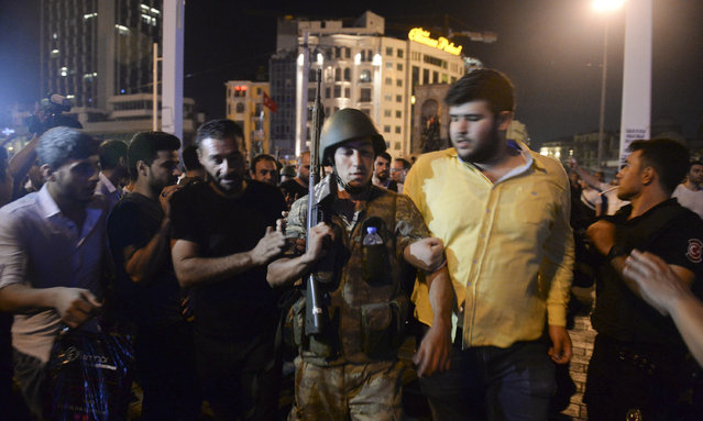 A Turkish soldier, arrested by civilians, is walked to be handed to police officers, in Istanbul's Taksim square, early Saturday, July 16, 2016. (Photo by Selcuk Samiloglu/AP Photo)