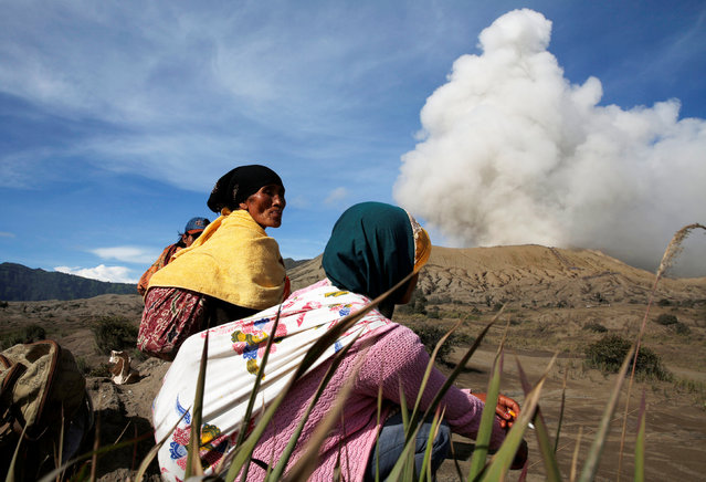Mount Bromo spews ash as Hindu villagers rest ahead of Kasada ceremony, when villagers and worshippers throw offerings such as livestock and other crops into the volcanic crater of Mount Bromo, in Probolinggo, Indonesia, July 20, 2016. (Photo by Reuters/Beawiharta)