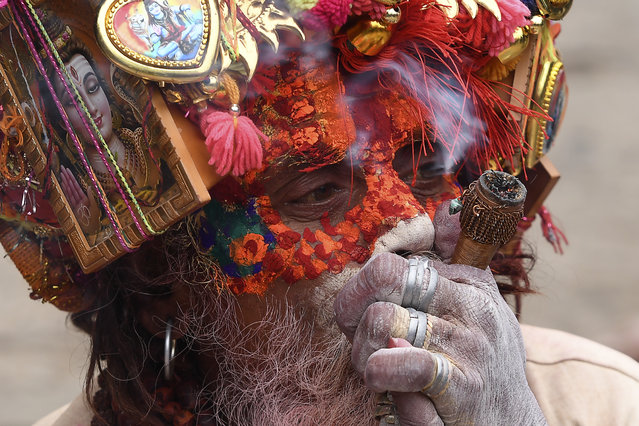 "A sadhu (Hindu holy man) smokes marijuana using a ""chillum"", a traditional clay pipe, as a holy offering during the Hindu festival ""Maha Shivaratri"" in Kathmandu on February  21, 2020. (Photo by Prakash Mathema/AFP Photo)"
