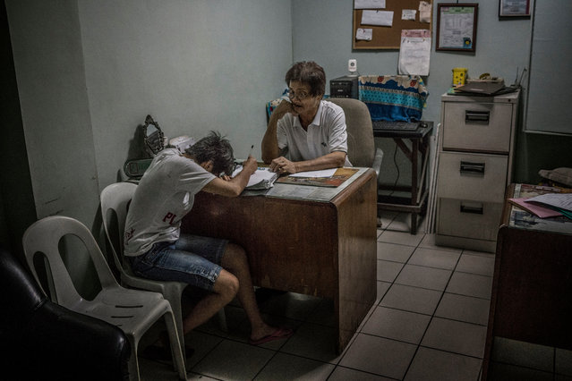 Ginnalyn Soriano breaks down in tears in front of Orly Fernandez, operations manager at Eusebio funeral home, as she fills out the required paperwork following the death of her brother Julius. (Photo by James Whitlow Delano/Funded by the Pulitzer Center on Crisis Reporting/The Guardian)