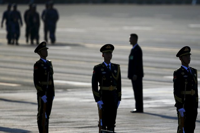 Soldiers and security guards arrive at the Tiananmen Square before a military parade to mark the 70th anniversary of the end of World War Two, in Beijing, China, September 3, 2015. (Photo by Damir Sagolj/Reuters)