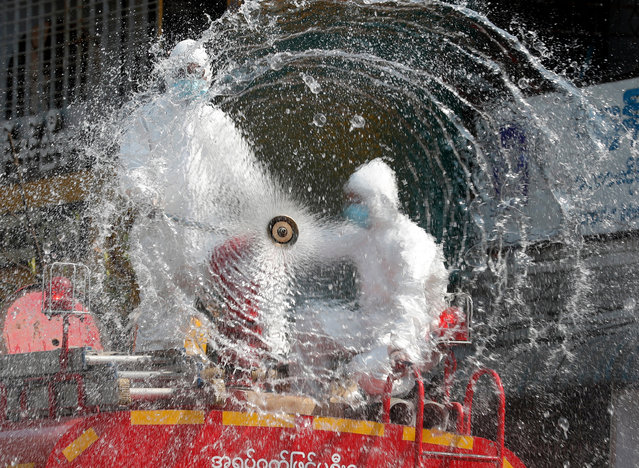 Firefighters spray disinfectant at a market to curb the spread of coronavirus in Yangon, Myanmar, 20 April 2020. Countries around the world are taking increased measures to stem the widespread of the SARS-CoV-2 coronavirus which causes the Covid-19 disease. (Photo by Nyein Chan Naing/EPA/EFE)