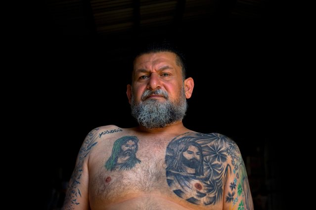 In this Tuesday, May 31, 2016 photo, Ali Hussein Nasreddine, 50, poses for a photo showing his tattoo of Shiite Muslims' first Imam Ali, and his son Imam Hussein, the grandson of the Prophet Muhammed in the southern suburb of Beirut, Lebanon. (Photo by Hassan Ammar/AP Photo)