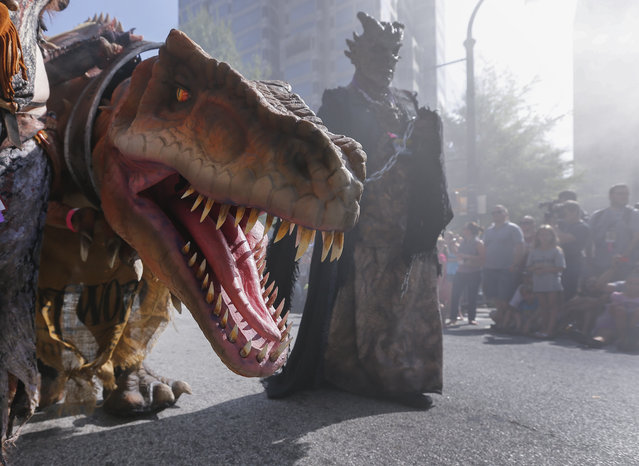 A character leading a dinosaur during the Dragon Con science fiction and fantasy parade in Atlanta, Georgia, USA, 30 August 2014. Thousands of people crowded downtown to watch the 28th annual science fiction and fantasy convention in Atlanta. (Photo by Erik S. Lesser/EPA)