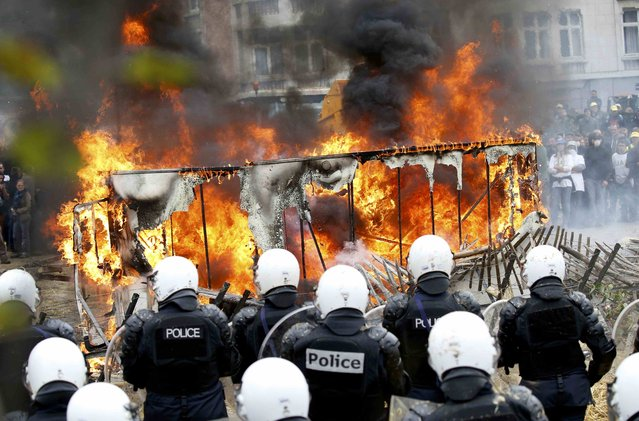 Belgian riot police officers stand guard next to a burning caravan during clashes as farmers and dairy farmers from all over Europe take part in a demonstration outside an European Union farm ministers emergency meeting at the EU Council headquarters in Brussels, Belgium, September 7, 2015. (Photo by Jacky Naegelen/Reuters)
