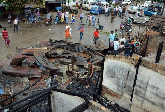 People stand next to the burnt shops after gunmen flung grenades in a market on Friday, on the outskirts of Kokrajhar town, in the northeastern state of Assam, India, August 6, 2016. (Photo by Reuters/Stringer)