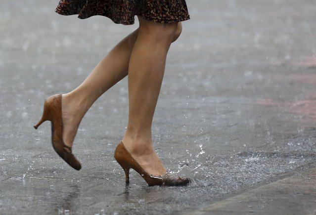 A woman walks in heavy rain caused by typhoon Etau in Tokyo's business district September 9, 2015. Typhoon Etau made landfall in central Japan on Wednesday morning, bringing strong winds and heavy rains as authorities warned of possible landslides and flooding, local media reported. (Photo by Toru Hanai/Reuters)