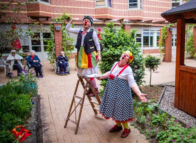 """Kerstin Daum as """"Kiki"""" and Ines Vowinkel (l) as """"Fine"""" play as clinic clowns in front of residents on the inner courtyard of the closed old people's and nursing home """"Augustenstift"""" in Schwerin, Gemany on May 19, 2020. Due to corona protection measures, the two clowns are only allowed to play in front of balconies and on terraces in front of the house. (Photo by Jens Büttner/dpa-Zentralbild/dpa)"""