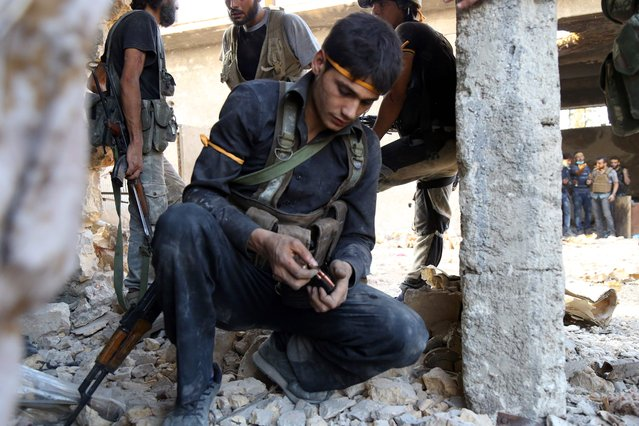 A rebel fighter reloads the magazine of his weapon during clasahes with regime forces  in Ramussa on the southwestern edges of Syria's northern city of Aleppo on August 6, 2016. Syrian rebels said they have broken a three-week government siege of second city Aleppo, turning the tables on Russian-backed regime forces who are now on the defensive. (Photo by Fadi Al-Halabi/AFP Photo)