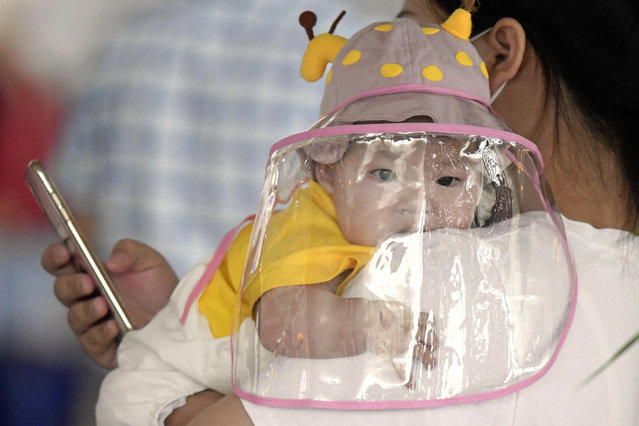 A baby with a face shield waits to board a plane at an airport in Wuhan, central China's Hubei Province Saturday, May 23, 2020. China on Saturday reported no new confirmed cases or deaths from the new coronavirus. (Photo by Kyodo News via AP Photo)