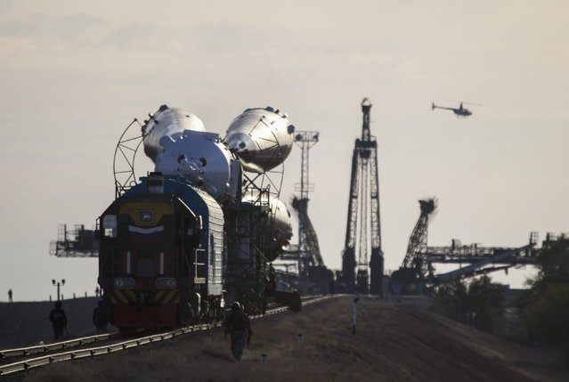 A helicopter flies past as the Soyuz TMA-14M spacecraft is transported to its launch pad at Baikonur cosmodrome September 23, 2014. The Soyuz is scheduled to carry Barry Wilmore of the U.S., Elena Serova and Alexander Samokutyaev of Russia to the International Space Station on September 26. (Photo by Shamil Zhumatov/Reuters)