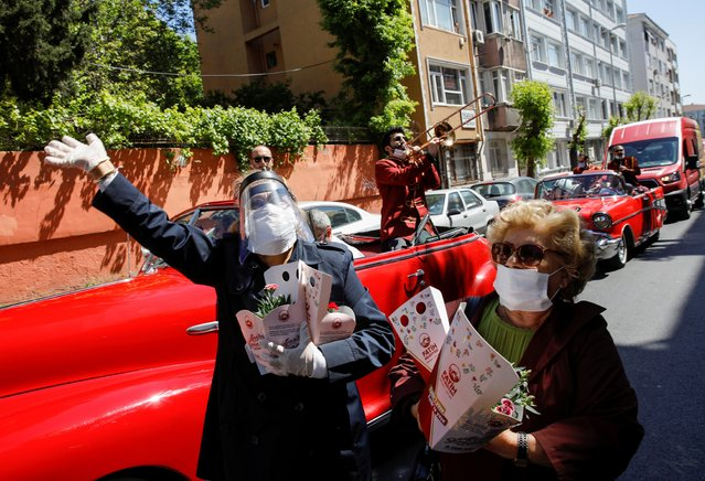 Locals listen to a band singing along a street and receive flowers from volunteers as a convoy of Fatih Municipality celebrates Mother's Day during a curfew amid the spread of the coronavirus disease (COVID-19), in Istanbul, Turkey, May 10, 2020. (Photo by Umit Bektas/Reuters)