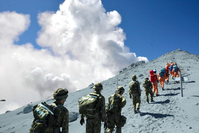 This handout picture taken by Joint Staff on September 28, 2014 and released on September 29 shows Japan's Self Defense Force soldiers and rescue workers searching for survivors and missing climbers on the ash covered top of Mount Ontake at Nagano prefecture, one day after Japan's volcano Ontake erupted in central Japan, which straddling Nagano and Gifu prefecture. (Photo by AFP Photo/Joint Staff)