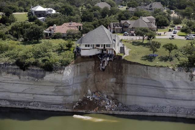 Crews prepare to set a house on fire, days after part of the ground it was resting on collapsed into Lake Whitney, Texas June 13, 2014. (Photo by Brandon Wade/Reuters)