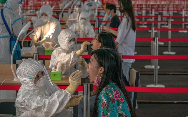 People are tested for COVID-19 at a makeshift coronavirus testing center, in Beijing, China, 24 June 2020. Almost three million of people were tested for COVID-19 in Beijing as the city continues the mass testing for the disease. (Photo by Roman Pilipey/EPA/EFE)