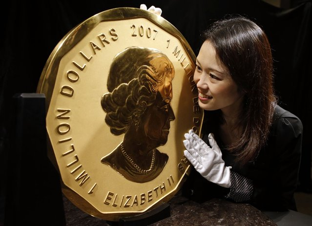 An oversize 100kg Maple Leaf gold coin bearing the profile of Queen Elizabeth II and measuring 53 cm (20.8 inches) in diameter by jeweler Ginza Tanaka is on display in Tokyo, Japan, November 6, 2012. At prevailing prices, the intrinsic value of the gold in the coin weighing 3,215 troy ounces at US$1,711.30 per ounce is worth US$5,501,829.50. (Photo by Toru Hanai/Reuters)