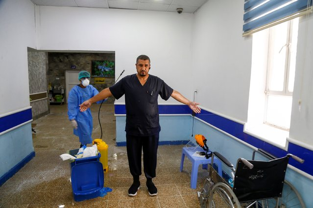Iraqi doctor Haidar Ali Musa al-Hasani, internal medicine specialist, is disinfected after checking on cases of the coronavirus disease (COVID-19), at Al-Hakim Hospital in the holy city of Najaf, Iraq on June 19, 2020. (Photo by Alaa Al-Marjan/Reuters)