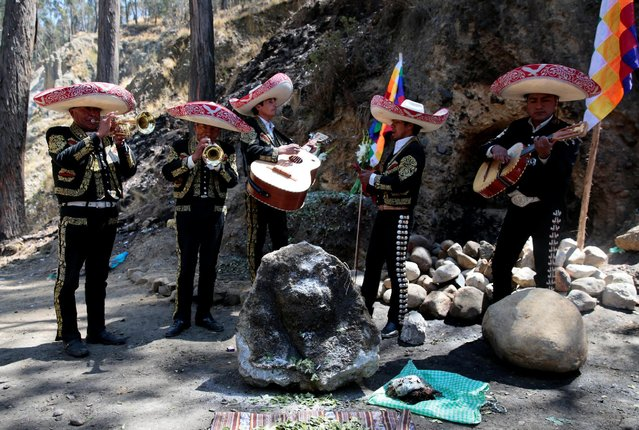 """A Mariachi group performs in honor of a stone which bears an impression that locals refer to as """"Devil face"""", as a shrine frequented by indigenous witch doctors was removed to expand a main highway between La Paz and El Alto, Bolivia, August 24, 2016. (Photo by David Mercado/Reuters)"""
