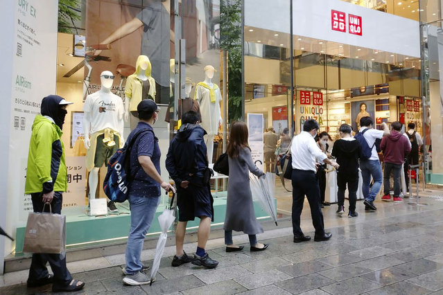 People wait in line at a Uniqlo clothing store at Ginza shopping area in Tokyo, Friday, June 19, 2020. Japanese shoppers queued up in a long line at Uniqlo stores and others clogged up the company's online shopping site Friday as they rushed to buy washable face masks made from the fashion brand's fabric for popular underwear line for summertime use. (Photo by Kyodo News via AP Photo)