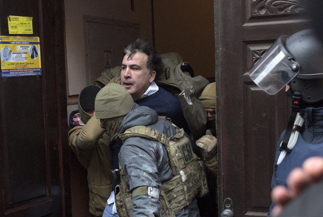 The Ukrainian Security Service officers detain Mikheil Saakashvili at the entrance of his house in Kiev, Ukraine, Tuesday, December 5, 2017. Ukraine's intelligence agency on Tuesday detained the former president of Georgia who has emerged as an anti-corruption campaigner in his new country but faced an angry backlash of protesters who would not let the officers to take him away. (Photo by Evgeniy Maloletka/AP Photo)