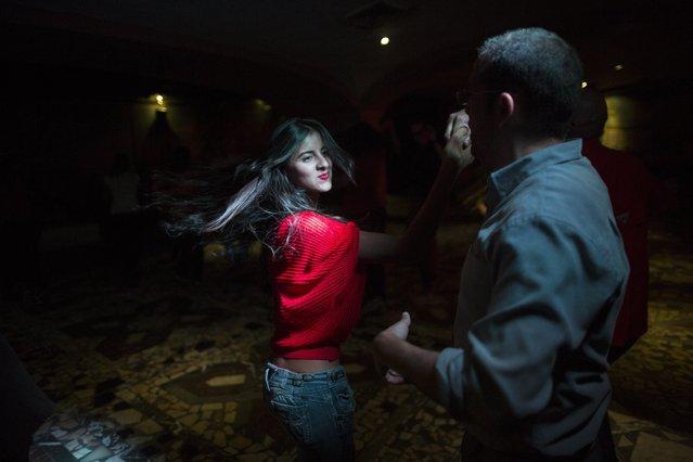 People salsa dance at a club in the financial district of Caracas, Venezuela, Thursday, October 26, 2017. (Photo by Rodrigo Abd/AP Photo)