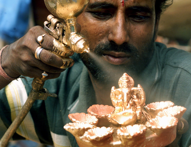 Subir Paul, an Indian worker, sprays paint while working on an idol of the Hindu elephant god Ganesh in the eastern Indian city of Calcutta on October 21, 2003. Earthen lamps are sold in large numbers during Diwali, the annual Hindu festival of lights. (Photo by Sucheta Das/Reuters)