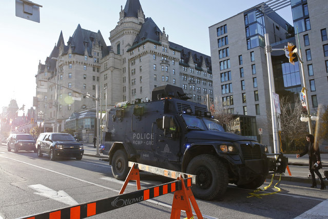 A Royal Canadian Mounted Police vehicle passes the Fairmont Chateau Laurier as it leaves a secure area downtown following shootings in Ottawa October 22, 2014. (Photo by Blair Gable/Reuters)