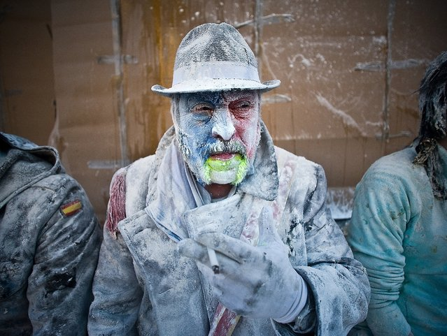 "A Reveller smokes during the battle of ""Enfarinats"", a flour fight in celebration of the Els Enfarinats festival. (Photo by David Ramos)"