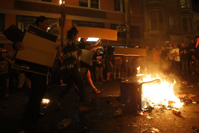 Revellers add fuel to a street bonfire in celebration in San Francisco, California October 29, 2014. (Photo by Stephen Lam/Reuters)