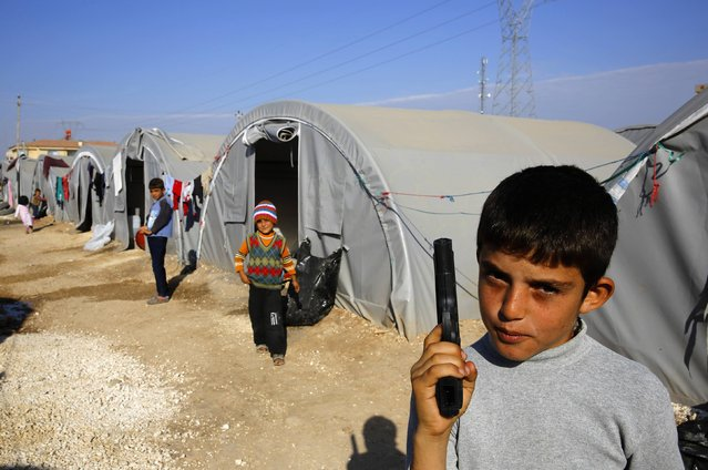 A young Kurdish refugee from Kobani holds a toy pistol at a Kurdish refugee camp in the border town of Suruc, Sanliurfa province October 27, 2014. (Photo by Yannis Behrakis/Reuters)