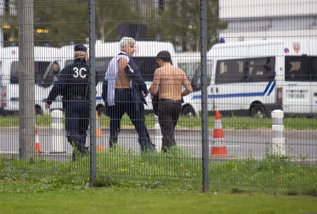 Air France director of Human Ressources, Xavier Broseta, right, and Air France assistant director long-haul flight, Pierre Plissonnier, center, are protected by a police officer as they flee Air France headquarters at Roissy Airport, north of Paris, after scuffles with union activist, Monday, October 5, 2015. Union activists protesting proposed layoffs at Air France stormed the headquarters during a meeting about the job cuts, zeroing in on two managers who had their shirts torn from their bodies. (Photo by Jacques Brinon/AP Photo)