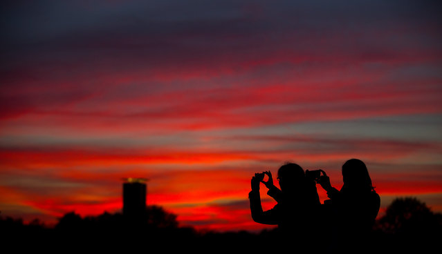 People take pictures of the sunset in Berlin October 27, 2014. (Photo by Hannibal Hanschke/Reuters)