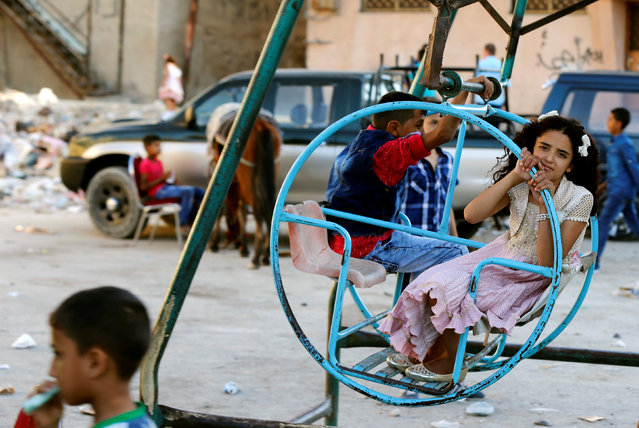 Palestinian children play on a mini ferris wheel, during the first day of the Muslim holiday Eid al-Adha at Al-Baqaa Palestinian refugee camp, near Amman, Jordan September 12, 2016. (Photo by Muhammad Hamed/Reuters)