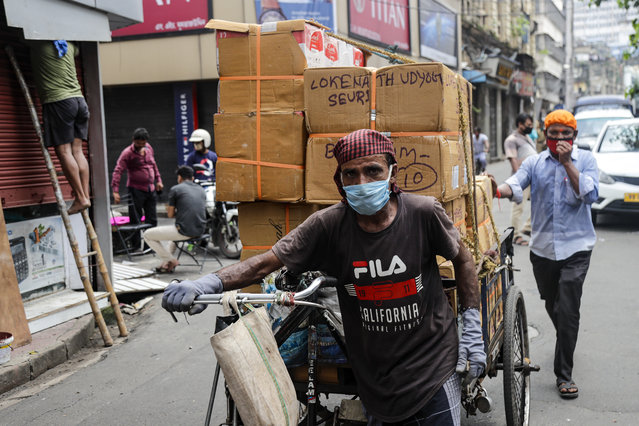 People wearing face mask carry materials for delivery on a transport rickshaw in Kolkata, India, Saturday, August 22, 2020. India now has the fourth most fatalities behind the United States, Brazil and Mexico. (Photo by Bikas Das/AP Photo)