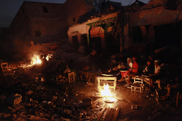 Earthquake survivors sit around a fire in downtown Port-au-Prince, Friday, February 5, 2010. (Photo by Rodrigo Abd/AP Photo)