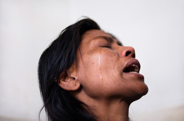 """""""Pobitra Tapa mourns alone in agony, painful tears of frustration for a life wasting away, withering from HIV and a tumor in her young body. She cried, away from the eyes of her already suffering husband who has been looking after her for several weeks at the Pkohara hospital in Nepal. Losing any sense of hope, this mother of two was once an alcoholic and suspects that she got HIV-tainted blood in a transfusion years ago. (Photo and comment by Miguel Candela, Spain/2013 Sony World Photography Awards"""