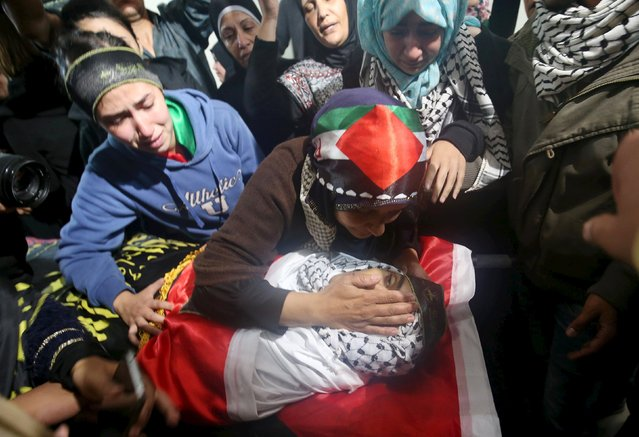 The mother of Palestinian man Mohnad Halabi, who was killed after stabbing and killing an off-duty Israeli soldier and a rabbi in Jerusalem's Old City on Saturday, touches his body during his funeral near the West Bank city of Ramallah October 9, 2015. (Photo by Mohamad Torokman/Reuters)