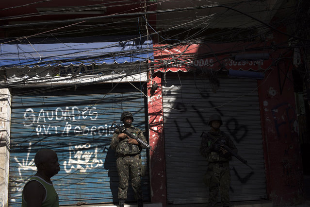 A soldier stands guard during a surprise operation in the Manguinhos slum in Rio de Janeiro, Brazil, Thursday, January 18, 2018. (Photo by Leo Correa/AP Photo)