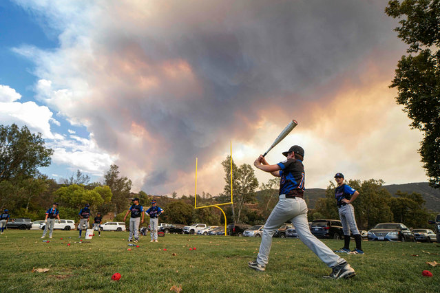 Little League players warm-up before a game as a brush fire is ablaze in back at a field next to the Sycuan Casino on the Sycuan Indian reservation during the Valley Fire, near Dehesa, in San Diego, California on September 6, 2020. The Valley Fire in the Japatul Valley burned 4,000 acres overnight with no containment and 10 structures destroyed, Cal Fire San Diego said. (Photo by Sandy Huffaker/AFP Photo)
