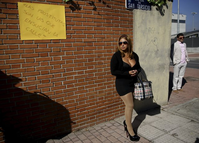 """A s*x worker (C) stages a performance to denounce what they say is abuse and social stigma against them in Madrid, Spain, October 14, 2015. Placard reads """"Prostitutes are the ones that make the streets dirty"""". (Photo by Andrea Comas/Reuters)"""