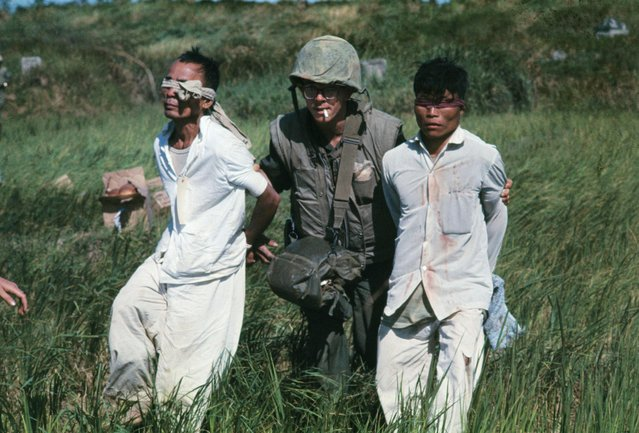 A US Marine leads two Viet Cong suspects in restraints during the Tet Offensive on February 20, 1967. (Photo by Bettmann Archive/Getty Images)