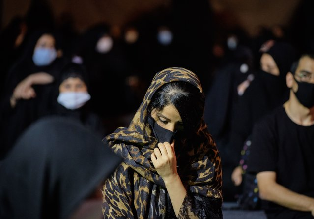 An Iranian Shiite Muslim wearing a protective face mask attends a Muharram mourning ceremony in southern Tehran on August 28, 2020. The new coronavirus (COVID-19) put the country in the red situation, and the health officials warned people for observing social distancing and health protocols in the Muharram mourning ceremonies and being ready for the third wave of the COVID-19 disease that will begin in the fall. (Photo by Morteza Nikoubazl/NurPhoto via Getty Images)