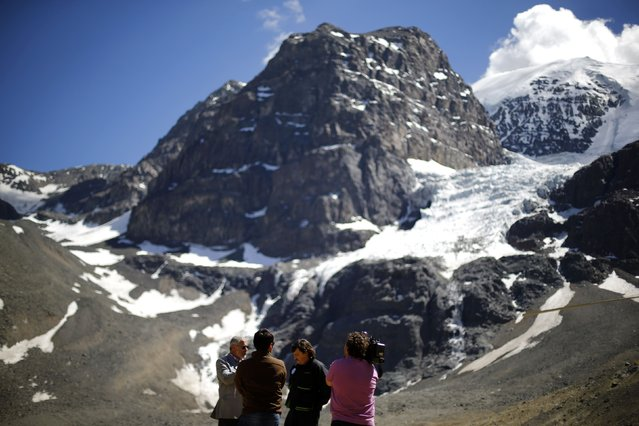 """Francisco Ferrando (rear L), a glaciologist, and Greenpeace director in Chile Matias Asun (rear R), speak with the media in front of """"La Paloma"""" glacier next to the open pits of CODELCO'S Andina and Anglo America's Los Bronces copper mines (not pictured) at Los Andes Mountain range, near Santiago city, November 17, 2014. (Photo by Ivan Alvarado/Reuters)"""