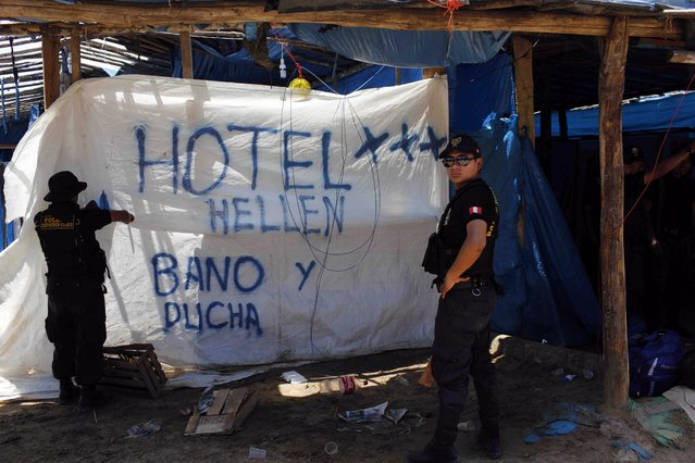 "In this November 11, 2014 photo, a policeman begins to rip apart a tarp advertising restroom and shower services for the ""Hotel Hellen"", set up in an illegal gold mining camp, occupied in an operation to eradicate illegal mining in the area known as La Pampa, in Peru's Madre de Dios region. (Photo by Rodrigo Abd/AP Photo)"