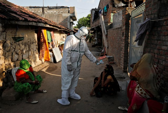 A healthcare worker wearing personal protective equipment (PPE) checks the temperature of a woman sitting outside her house in an alley during a door-to-door survey for the coronavirus disease (COVID-19), in Jakhan village in the western state of Gujarat, India, September 22, 2020. (Photo by Amit Dave/Reuters)